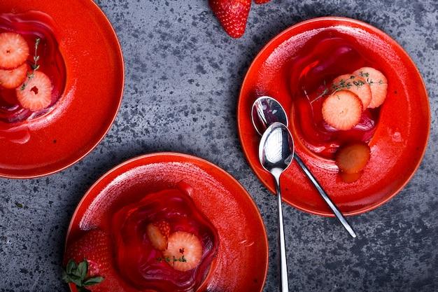 Gelatina de frutas con fresas frescas. comida sana. gelatina de fresa en plato blanco. postre de verano con mermelada de frutas