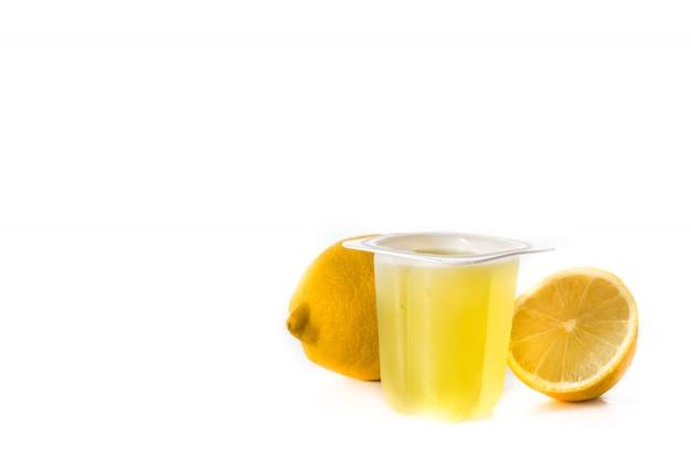 Gelatinas de limón en un vaso de plástico aislado en el espacio de copia de superficie blanca