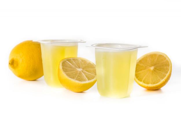 Gelatinas de limón en un vaso de plástico aislado en la superficie blanca