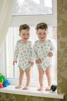 Gemelos alegres - hermanos de pie en el alféizar de una ventana