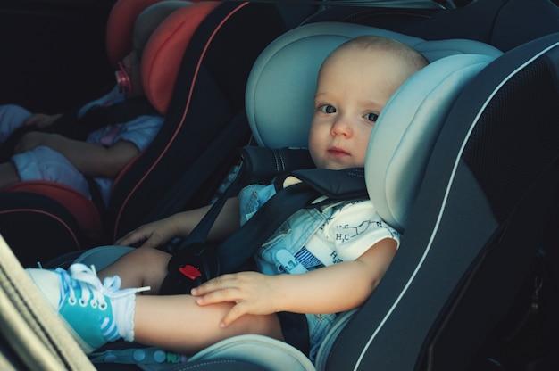 Gemelos niño y niña en asientos infantiles en el coche. transporte de seguridad para bebés. niños hasta un año.