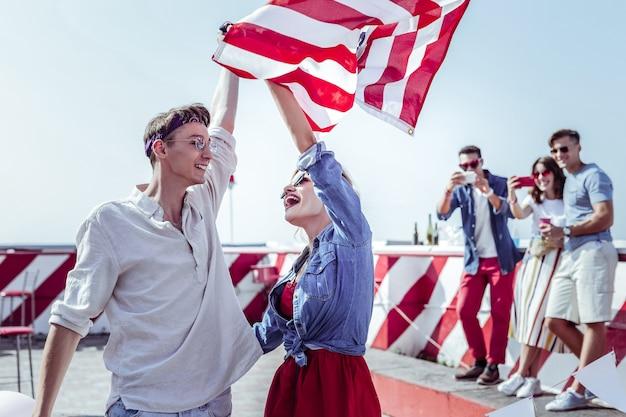 Generación joven. hombre guapo levantando la mano sosteniendo la bandera americana