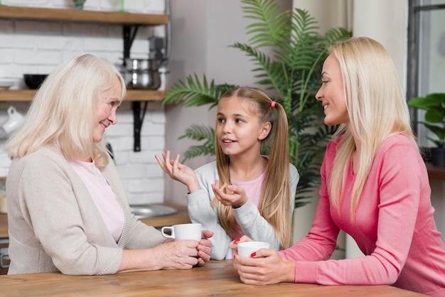 Generación de mujeres conversando en la cocina.