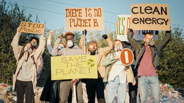 Generación se preocupa por el futurogrupo de voluntarios con máscaras de gas con un cartel llamando a cuidar ...