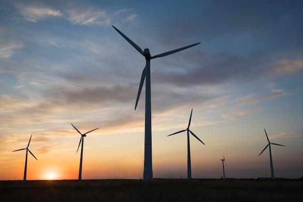 Generadores de energía de molinos de viento al atardecer del día.