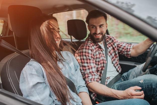 Gente agradable y alegre está sentada en el automóvil y viajando allí. guy lo conduce y mantiene las manos sobre el timón y la transmisión. la chica está sentada junto a él y se divierte.