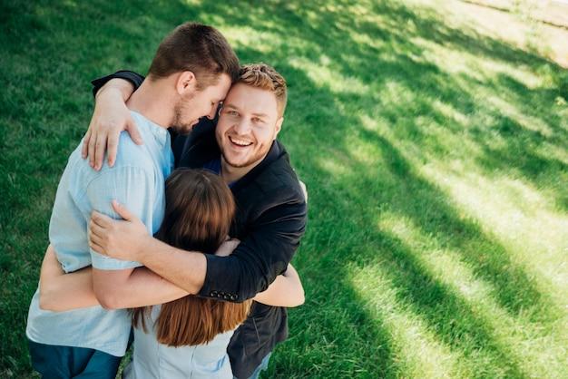 Gente alegre abrazando y sonriendo a la luz del sol