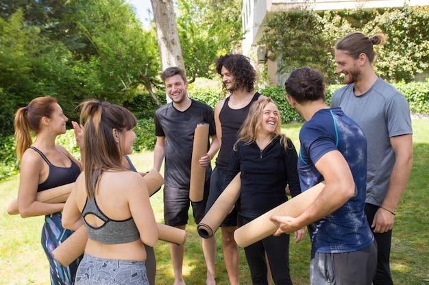 Gente alegre con colchonetas de yoga charlando y riendo.