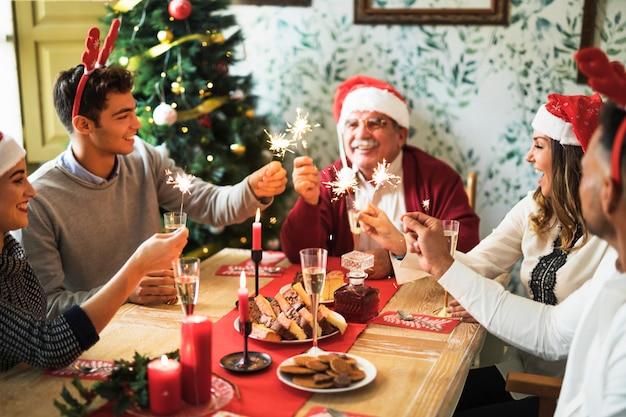 Gente alegre con fuego de bengala en mesa festiva