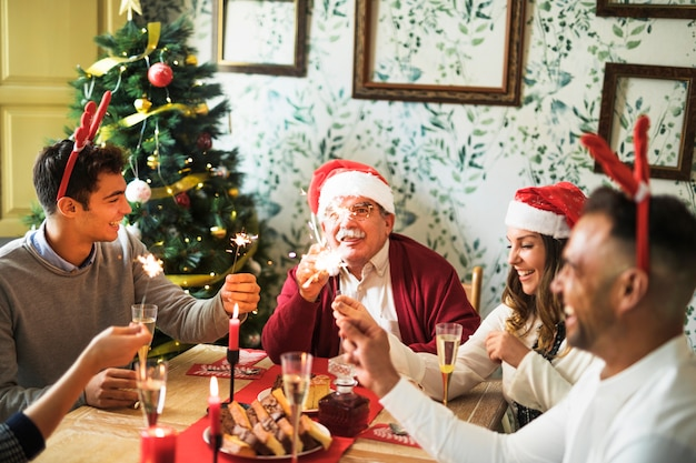 Gente alegre con fuegos de bengala en mesa festiva