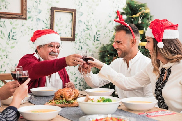 Gente alegre haciendo sonar las copas en la mesa navideña