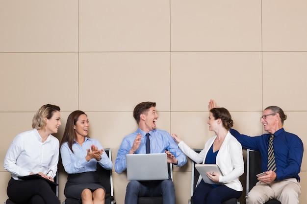 La gente alegre de negocios que felicita hombre joven