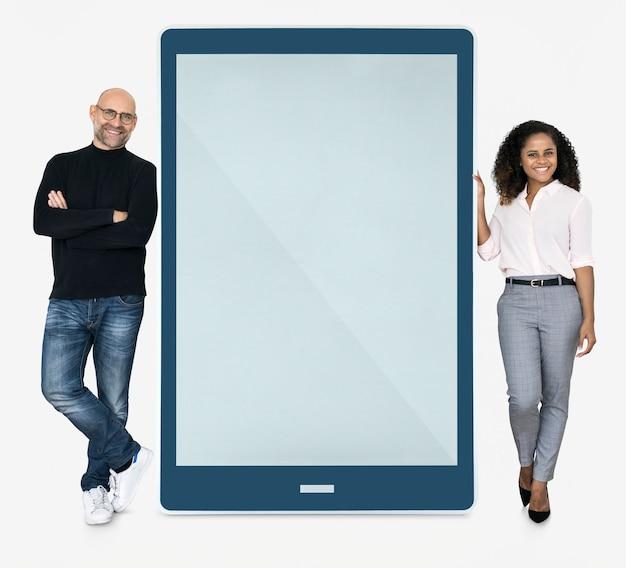 Gente alegre de pie al lado de una tableta