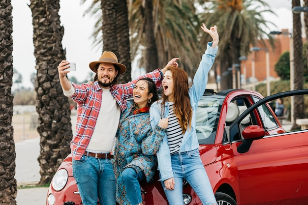 Gente alegre tomando selfie cerca de auto rojo en la calle