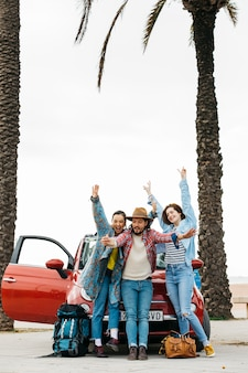 Gente alegre tomando selfie cerca de auto rojo