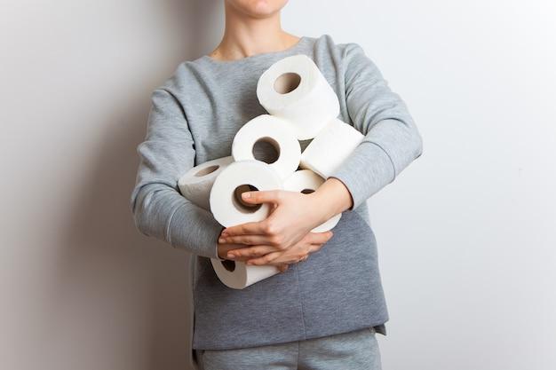 La gente está almacenando papel higiénico. la mujer sostiene muchos rollos de papel higiénico