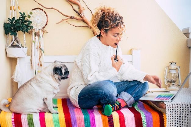 Gente alternativa en el trabajo hermosa mujer adulta en casa afuera en la terraza trabaja con tecnología computadora portátil y perro pug gordo mírala sentarse en un banco de moda de color