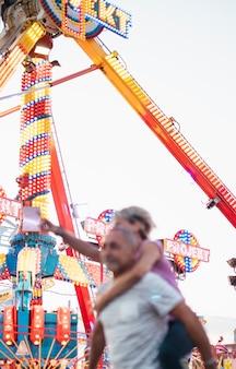 Gente de ángulo bajo divirtiéndose en el parque de atracciones