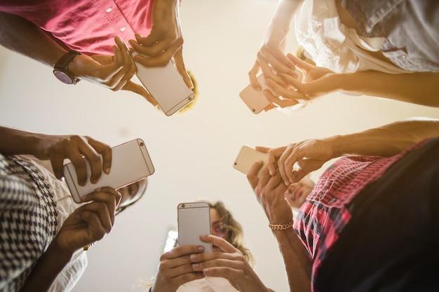 Gente anónima ocupada con teléfonos inteligentes