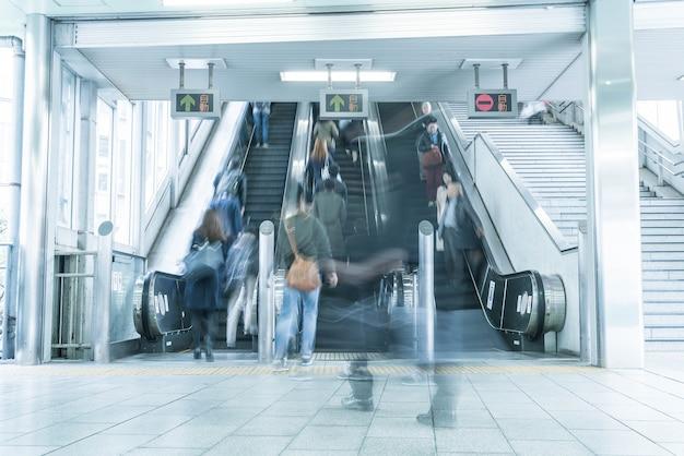 La gente se apresura en el movimiento de una escalera mecánica borrosa