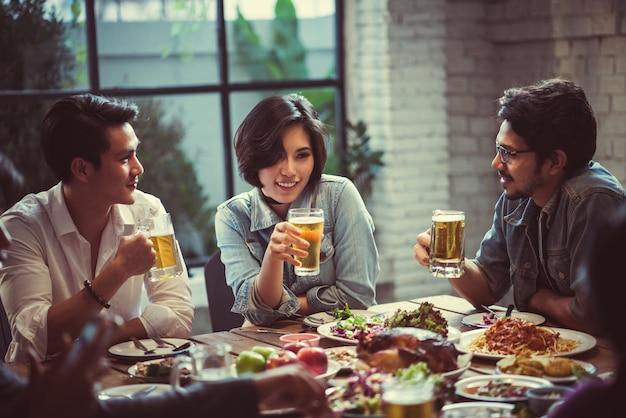 La gente en asia está celebrando el festival tintinean vasos cerveza y cena feliz