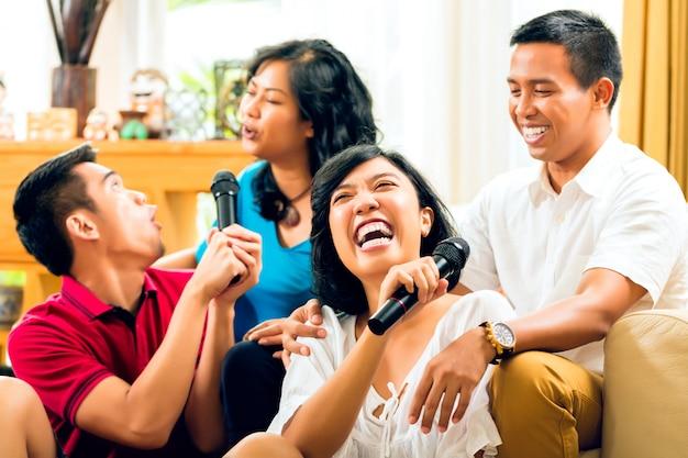 Gente asiática cantando en la fiesta de karaoke