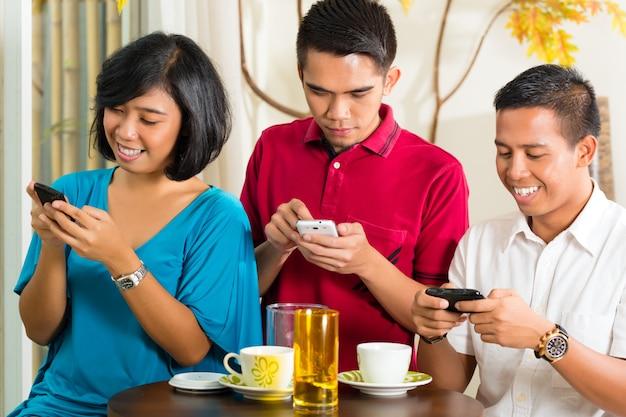 Gente asiática divirtiéndose con teléfono móvil