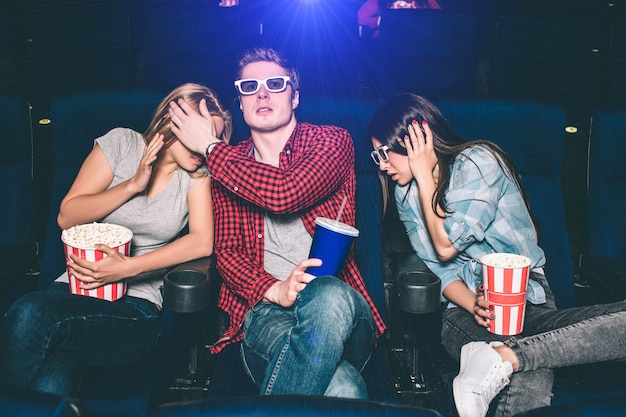La gente asustada y asustada está viendo películas en el cine. están sentados y mirando hacia adelante. todos tienen una canasta de palomitas de maíz o una taza con coca cola. no están solos en el pasillo.