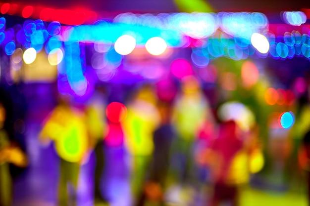 La gente baila, canta, diviértete y relájate en un fondo borroso de discoteca