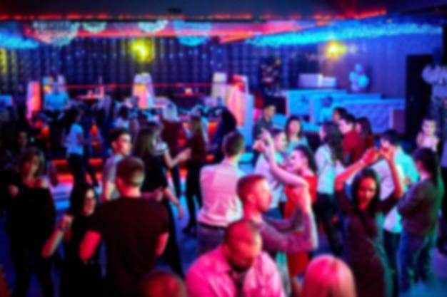 La gente baila en la pista de baile en una discoteca, mucha gente. luces estroboscópicas brillantes. no hay foco, fondo borroso