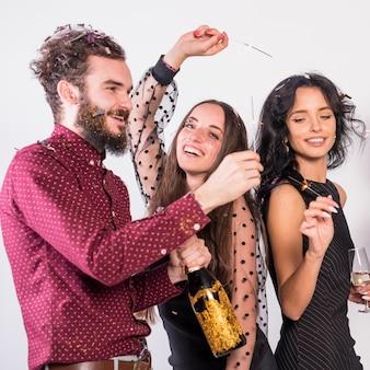 Gente bailando con bengalas en fiesta.