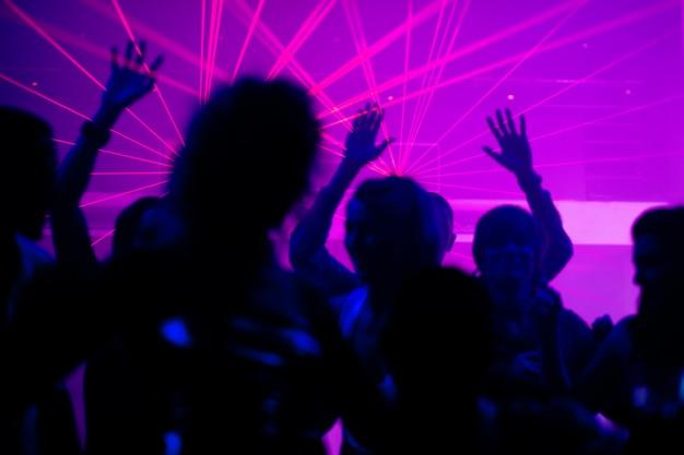 Gente bailando en club con láser.