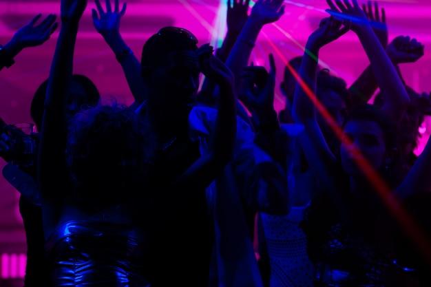 Gente bailando en el club con láser