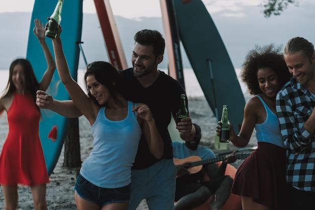 La gente está bailando en la playa. guitarrista afroamericano.