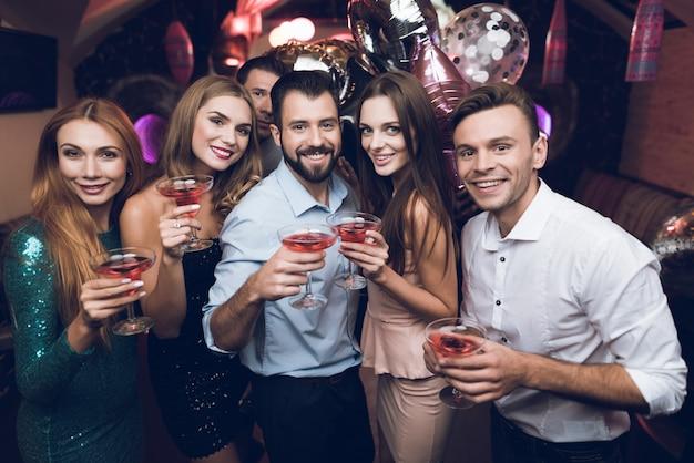La gente bebe cócteles y se divierte. se divierten.