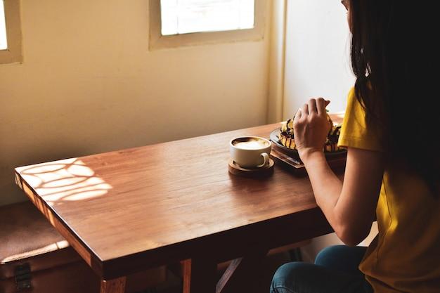 La gente está bebiendo café con leche en la mesa de madera con luz solar en la ventana