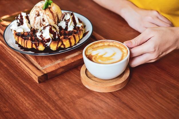 La gente está bebiendo café con leche en la mesa de madera