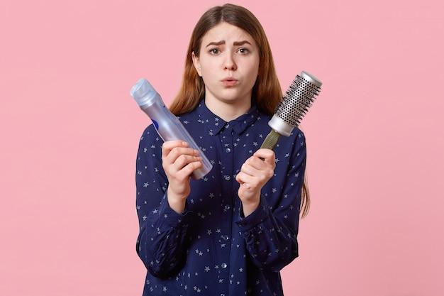 Gente, belleza, concepto de aseo. la joven disgustada pone mala cara con los labios vestidos con una camisa elegante, posa sobre la pared rosada, sostiene la laca y el peine, acude al peluquero para hacer el peinado.