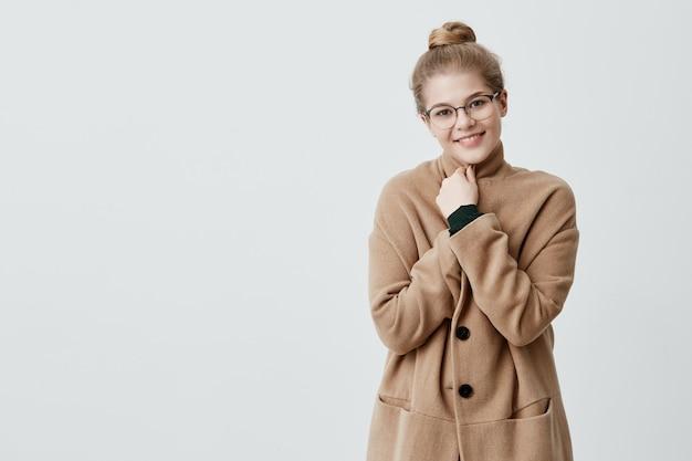 Gente, belleza y estilo de vida. sensual mujer con amplia sonrisa vestida con abrigo marrón sonriendo ampliamente siendo feliz de conocer a su mejor amigo. alegre bonita mujer con cabello rubio en nudo y elegantes anteojos.