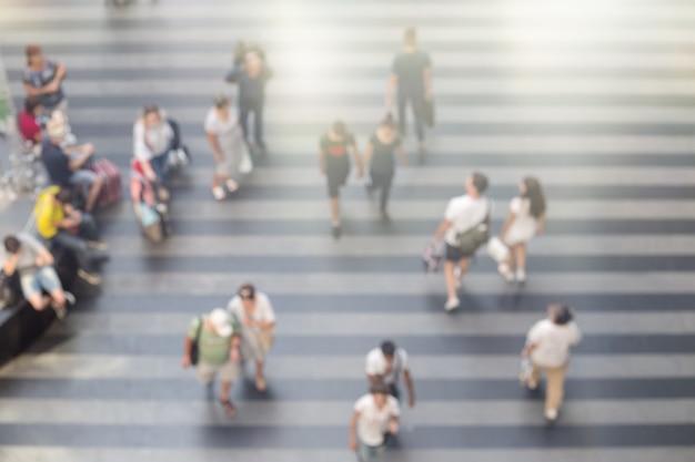 Gente borrosa caminando en el área de la estación de tren o terminal del aeropuerto.