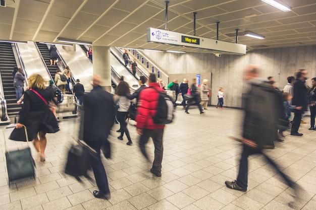 Gente borrosa caminando dentro de la estación de tren
