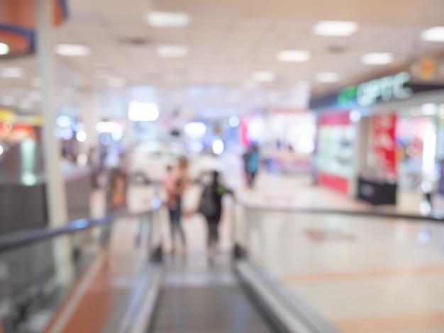 Gente borrosa en el centro comercial resumen antecedentes