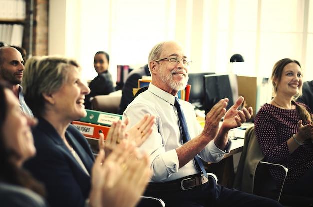 Gente de busiens aplaudiendo en una reunión.