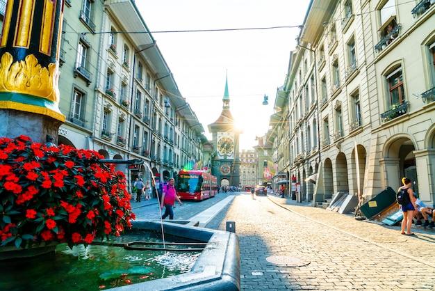 Gente en el callejón comercial con la torre del reloj astronómico zytglogge de berna en suiza