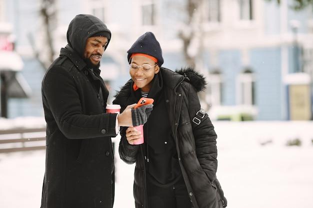 La gente camina afuera. día de invierno. pareja africana con café.