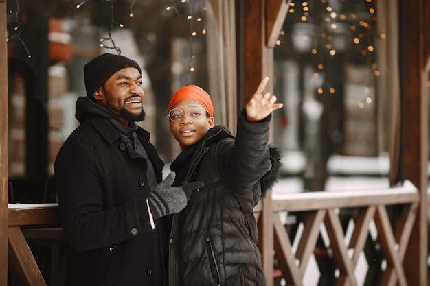 La gente camina afuera. día de invierno. pareja africana.