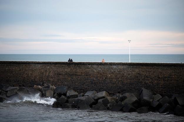 La gente camina sobre el rompeolas en san sebastian