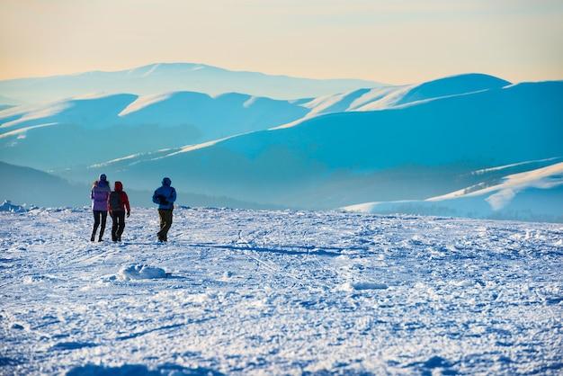 Gente caminando al atardecer en las montañas de invierno cubiertas de nieve