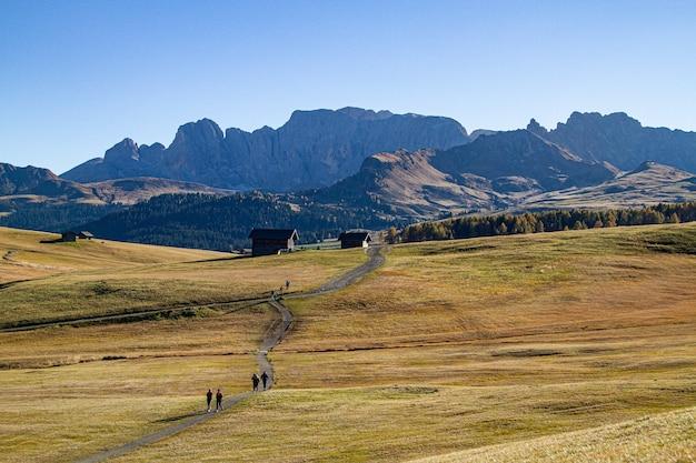 Gente caminando por un camino en medio de campos de hierba con edificios en la distancia