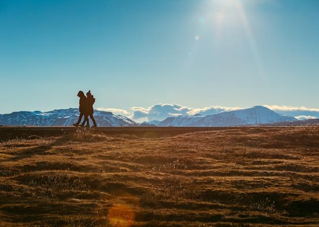 Gente caminando en un campo con hermosas colinas nevadas